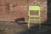 Old green chair next to an outdoor brick wall — Stock Photo