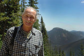 Smiling middle aged man near trees, mountains — Foto de Stock