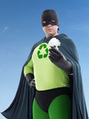 Eco superhero and CFL bulb — Photo