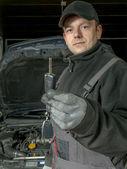 Auto mechanic with car key — Stock Photo