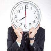 Businessman holding clock to show time — Stock Photo
