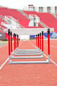 Hurdles on the red running track — Stock Photo