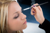 Girl applying make-up — Stock Photo