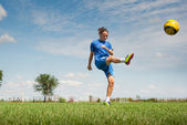 Girl kicking soccer ball — Stock Photo
