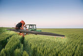 Tractor spraying on the field — Stock Photo