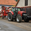 Red tractor with agro cultivator in the village — Stock Photo