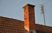 Orange roof tiles, chimney and old analog TV antenna — Stock Photo