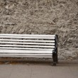 Empty white bench in front of wall — Stock Photo