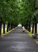 Oude vrouw loopt via het steegje in de stad — Stockfoto