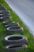 Old tyres are laid next to the empty road. — Stock Photo