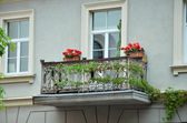 Retro balcony decorated by red flovers and green plants — Stock Photo