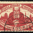 DANZIG - CIRCA 1923 A postage Stamp printing in Free City of Danzig (later Germany, now Gdansk, Poland) shows pensioner against the backdrop of the city , circa 1923 - Stock Photo