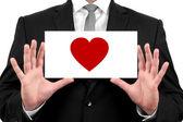 愛の心。黒のスーツのビジネスマンと黒のネクタイと白いシャツのビジネス カードを示しています。 — ストック写真