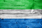 Sierra Leone Flag painted on old wood plank background — Foto Stock