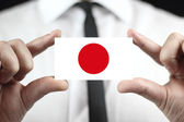 Businessman holding a business card with a Japan Flag — Stock Photo