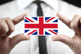 Businessman holding a business card with a UK Flag — Stock Photo