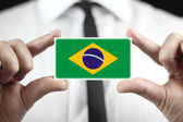 Businessman holding a business card with a Brazil Flag — Stock Photo