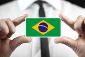 Empresario sosteniendo una tarjeta con una bandera de brasil — Foto de Stock