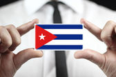 Businessman holding a business card with a Cuba Flag — Stock Photo