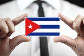 Empresario sosteniendo una tarjeta con una bandera de cuba — Foto de Stock