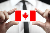 Businessman holding a business card with a Canada Flag — Stock Photo