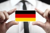 Businessman holding a business card with a Germany Flag — Foto de Stock