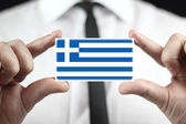Businessman holding a business card with a Greece Flag — Foto de Stock