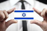 Businessman holding a business card with a Israel Flag — Stock Photo