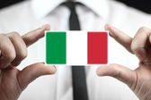 Businessman holding a business card with a Italy Flag — Foto de Stock