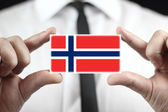 Businessman holding a business card with a Norway Flag — Stock Photo
