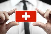 Empresario sosteniendo una tarjeta con una bandera de suiza — Foto de Stock