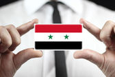 Businessman holding a business card with a Syria Flag — Stock Photo