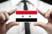 Empresario sosteniendo una tarjeta con una bandera de siria — Foto de Stock