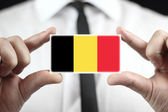 Businessman holding a business card with a Belgium Flag — Stock Photo