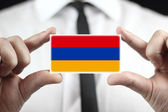 Businessman holding a business card with Armenia Flag — Stock Photo