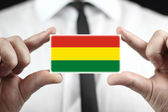 Businessman holding a business card with Bolivia Flag — Stock Photo