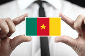 Businessman holding a business card with a Cameroon Flag — Stock Photo