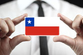 Businessman holding a business card with Chile Flag — Stock Photo