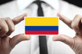 Businessman holding a business card with a Colombia Flag — Stock Photo