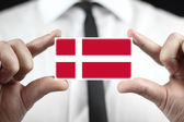 Businessman holding a business card with a Denmark Flag — Stock Photo
