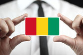 Businessman holding a business card with a Guinea Flag — Stock Photo