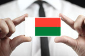 Businessman holding a business card with a Madagascar Flag — Stock Photo