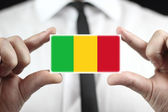 Businessman holding a business card with a Mali Flag — Stock Photo