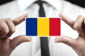 Businessman holding a business card with a Romania Flag — Stock Photo