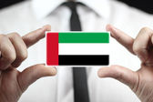 Businessman holding a business card with a United Arab Emirates Flag — Stock Photo