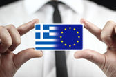 Businessman holding a business card with Greece and EU Flag — Stock Photo
