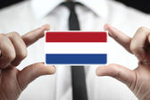 Businessman holding a business card with The Netherlands Flag — Stock Photo