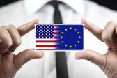 Businessman holding a business card with USA and EU Flag — Stock Photo