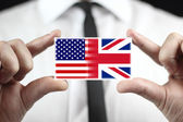 Businessman holding a business card with USA and UK Flag — Stock Photo