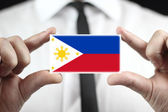 Businessman holding a business card with Philippines Flag — Stock Photo